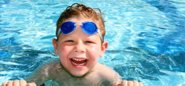 Kleiner Junge mit Schwimmbrille im Freibad