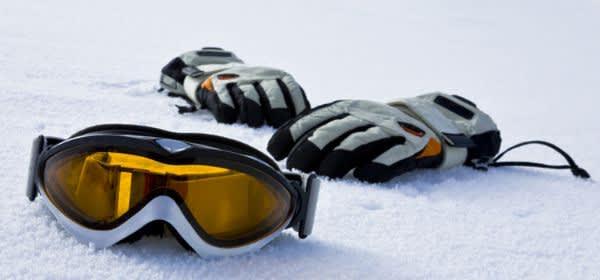 Skibrille und -handschuhe im Schnee