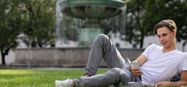 Junger Mann mit Smartphone vor dem Brunnen an der LMU