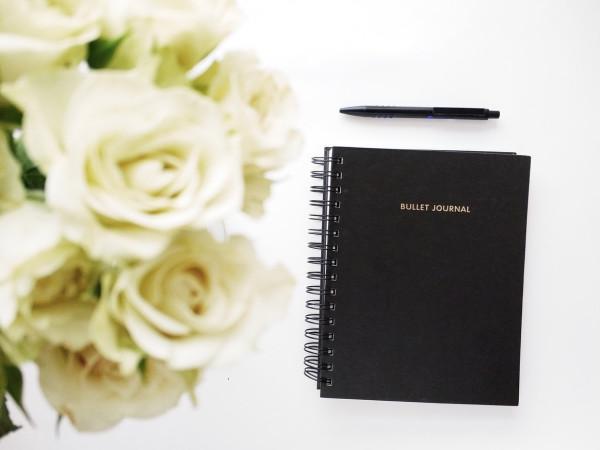 Buch mit Stifit unter einem Blumenstrauß