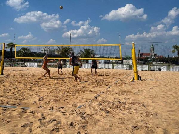 Vier Sportler und Sportlerinnen spielen gemeinsam Beachvolleyball auf dem Platz auf der Theresienwiese