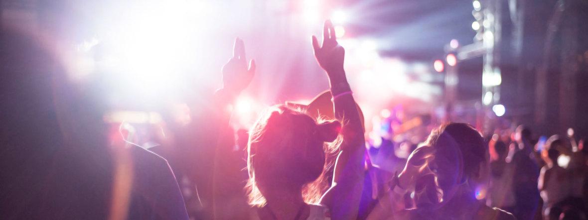 Leute auf einer Tanzfläche mit in die Luft gereckten Händen
