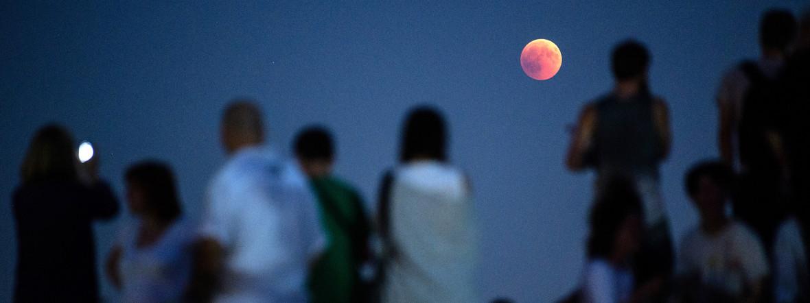 Zahlreiche Menschen beobachten am Olympiaberg die Mondfinsternis mit dem rötlichen Vollmond, Foto: picture alliance/Matthias Balk/dpa
