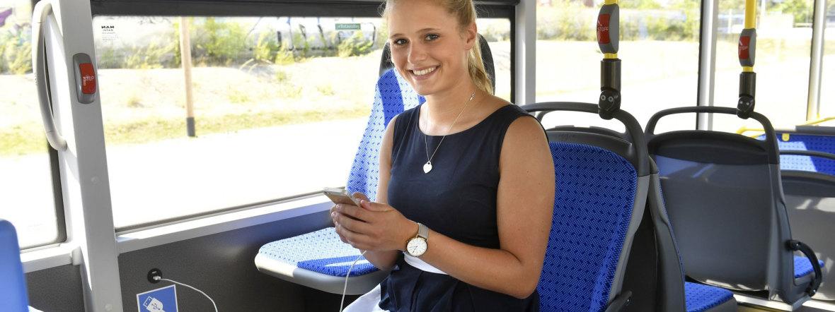 Frau im Bus lädt ihr Handy, Foto: SWM/MVG