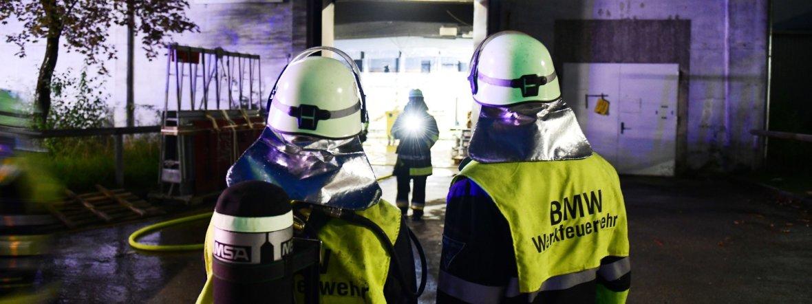 Einsatzkräfte der BMW-Werksfeuerwehr stehen vor einer Halle auf dem Werksgelände., Foto: dpa/Tobias Hase