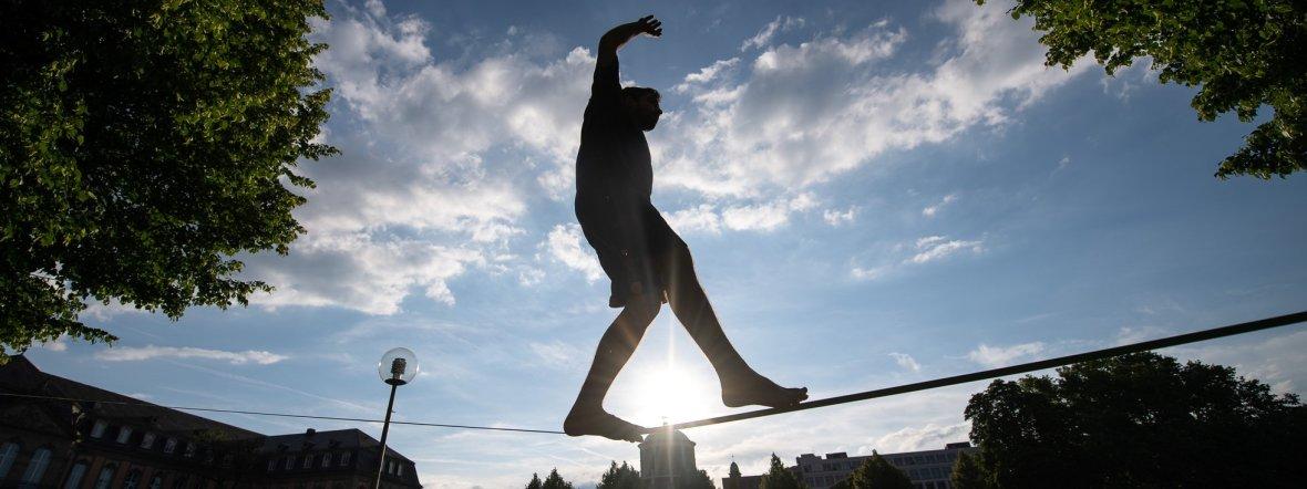 Ein Sportler balanciert auf einer Slackline., Foto: dpa/Sebastian Gollnow/Archivbild