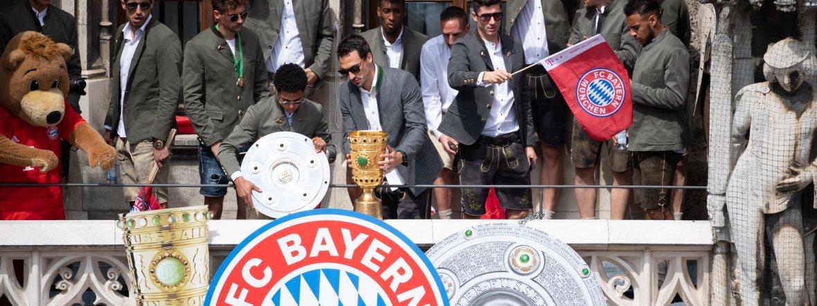 Bayern-Spieler auf dem Balkon des Rathauses am Marienplatz mit der Meisterschale und dem  DFB-Pokal., Foto: dpa/Sven Hoppe