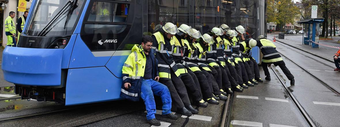 Feuerwehrmänner helfen, die Tram zuück ins Gleis zu bekommen., Foto: Berufsfeuerwehr München
