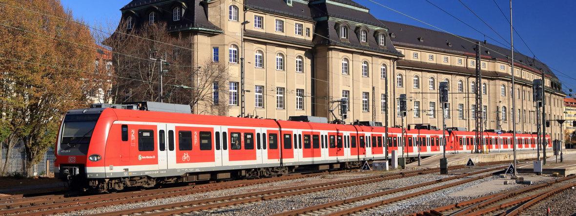 Eine S-Bahn fährt vor dem ehemaligen Bundesbahn-Zentralamt in der Arnulfstraße, Foto: Deutsche Bahn AG / Uwe Miethe