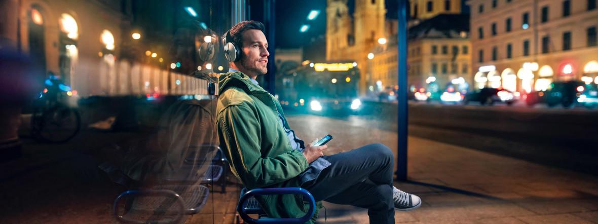 Mann mit Kopfhörern an einer Bushaltestelle, Foto: MVG