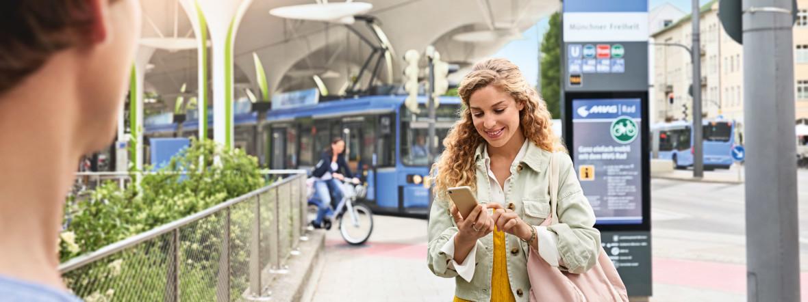 Frau an einer Haltestelle schaut aufs Handy, Foto: MVG