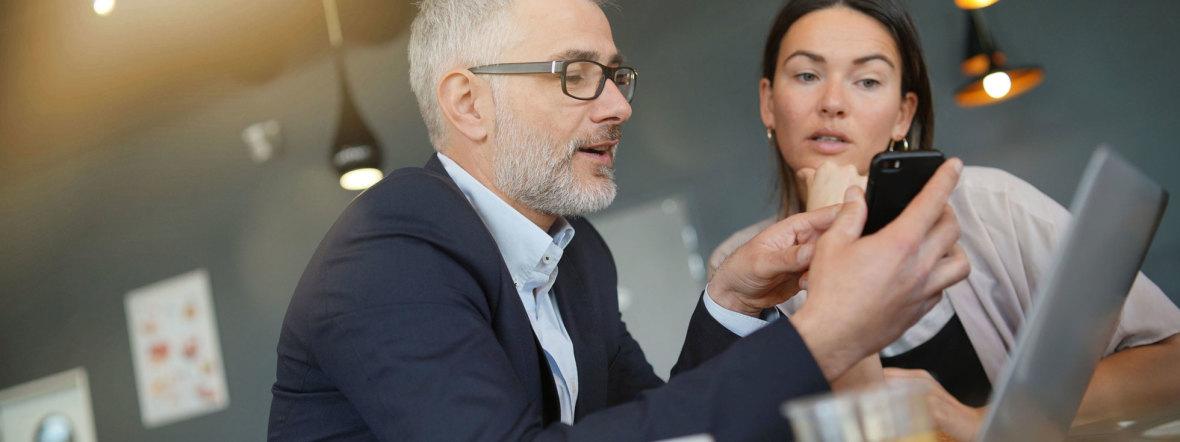 Geschäftsfrau und Geschäftsmann diskutieren vor Laptop, Foto: goodluz / Fotolia.com
