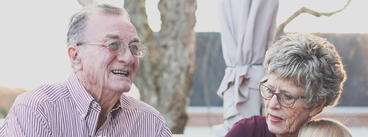 Zwei ältere Menschen mit einem Kind auf dem Schoß, Foto: Pexels
