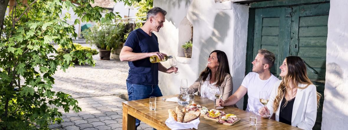 Mann schenkt an einem gedeckten Tisch Gästen Wein ein, Foto: Weinviertel Tourismus / Robert Herbst