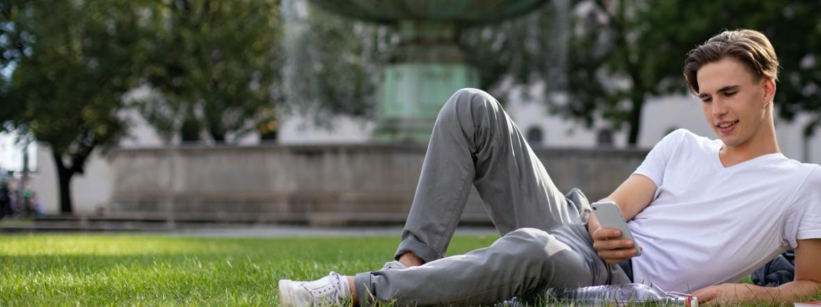 Junger Mann mit Smartphone vor dem Brunnen an der LMU, Foto: Stadtsparkasse München